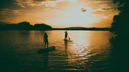 日落泛舟湖面的人剪影